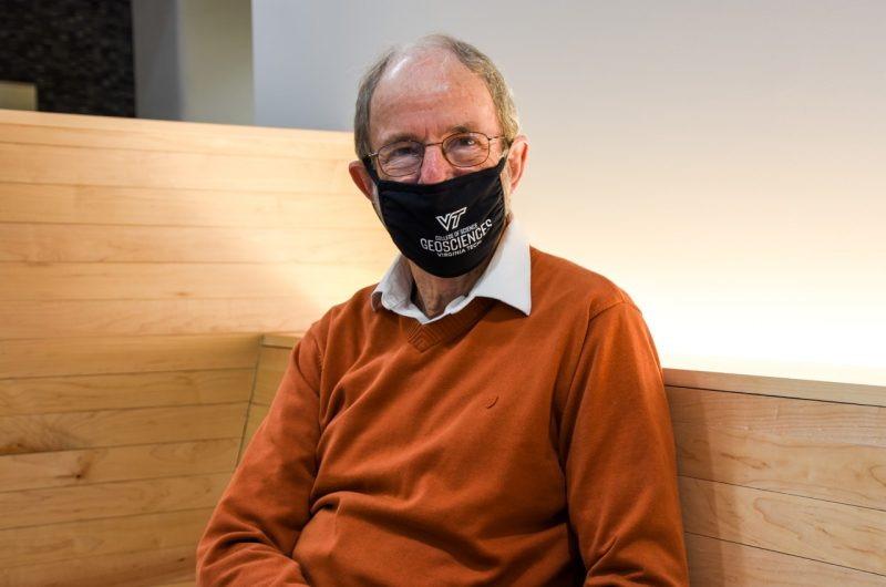 Kenneth Eriksson, wearing mask with the Department of Geosciences logo, poses for a photograph whilst sitting down.
