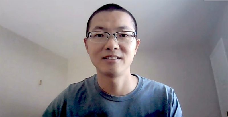 Guang Zhai, wearing a blue t-shirt, from his office in Berkeley, California, during a Zoom call. Screenshot by Steven Mackay.